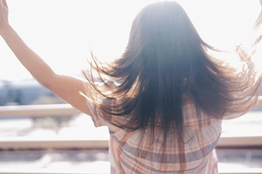 Woman holding arms up in sunshine