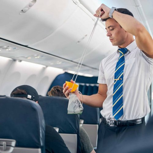 Man with oxygen mask demonstrating safety procedure prior to passenger airplane flight